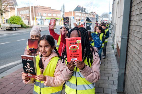 Leerlingen helpen met de verhuis van de oude naar de nieuwe bibliotheek.