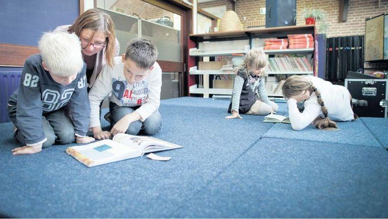 Leerlingen uit groep 8 van basisschool De Huve in Almelo lezen samen met kinderen uit groep 4. De juf komt kijken hoe het gaat. ©HERMAN ENGBERS Beeld
