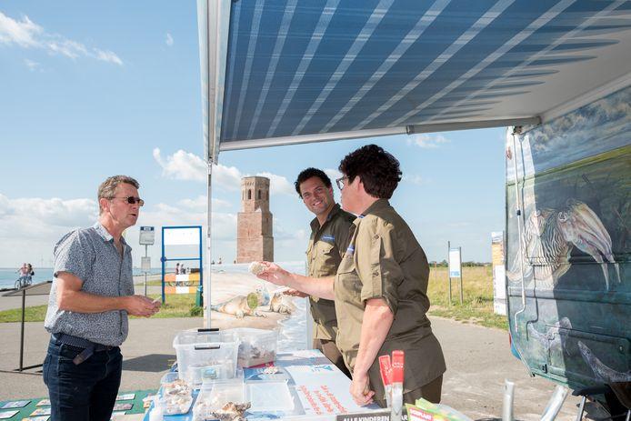 Ronnie Verrijzer in gesprek met boswachter Paul Begijn en Deltawachter Heleen Verduijn-de Hullu voor de Deltawagen aan de voet van de Plompe Toren bij Burghsluis