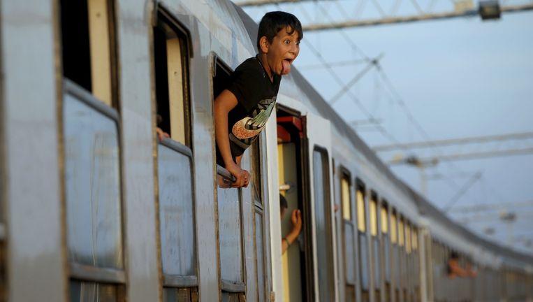 Een jonge vluchteling steekt zijn tong uit vanuit de trein bij Tovarnik, Kroatië. Beeld reuters