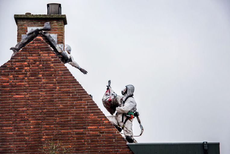 Asbest wordt van het dak van gehaald door mannen in witte pakken Beeld Raymond Rutting / de Volkskrant
