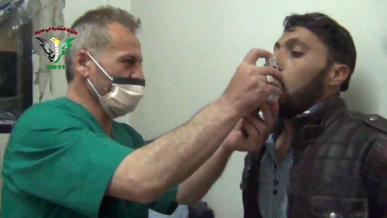 Een Syrische man wordt met een inhaler behandeld in Kfar Zeita. Hij zou slachtoffer zijn van een aanval met chloorgas. Beeld ap