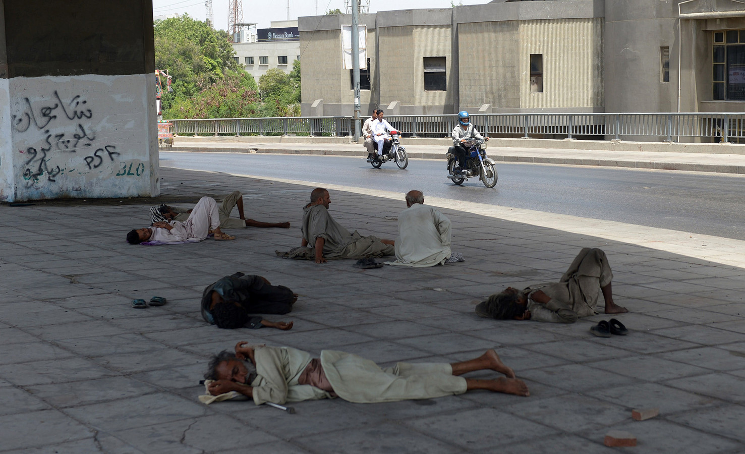 Mannen in het Pakistaanse Karachi zoeken beschutting onder een brug tijdens de hittegolf van 2015. Duizenden mensen, onder wie veel daklozen, kwamen destijds om het leven.