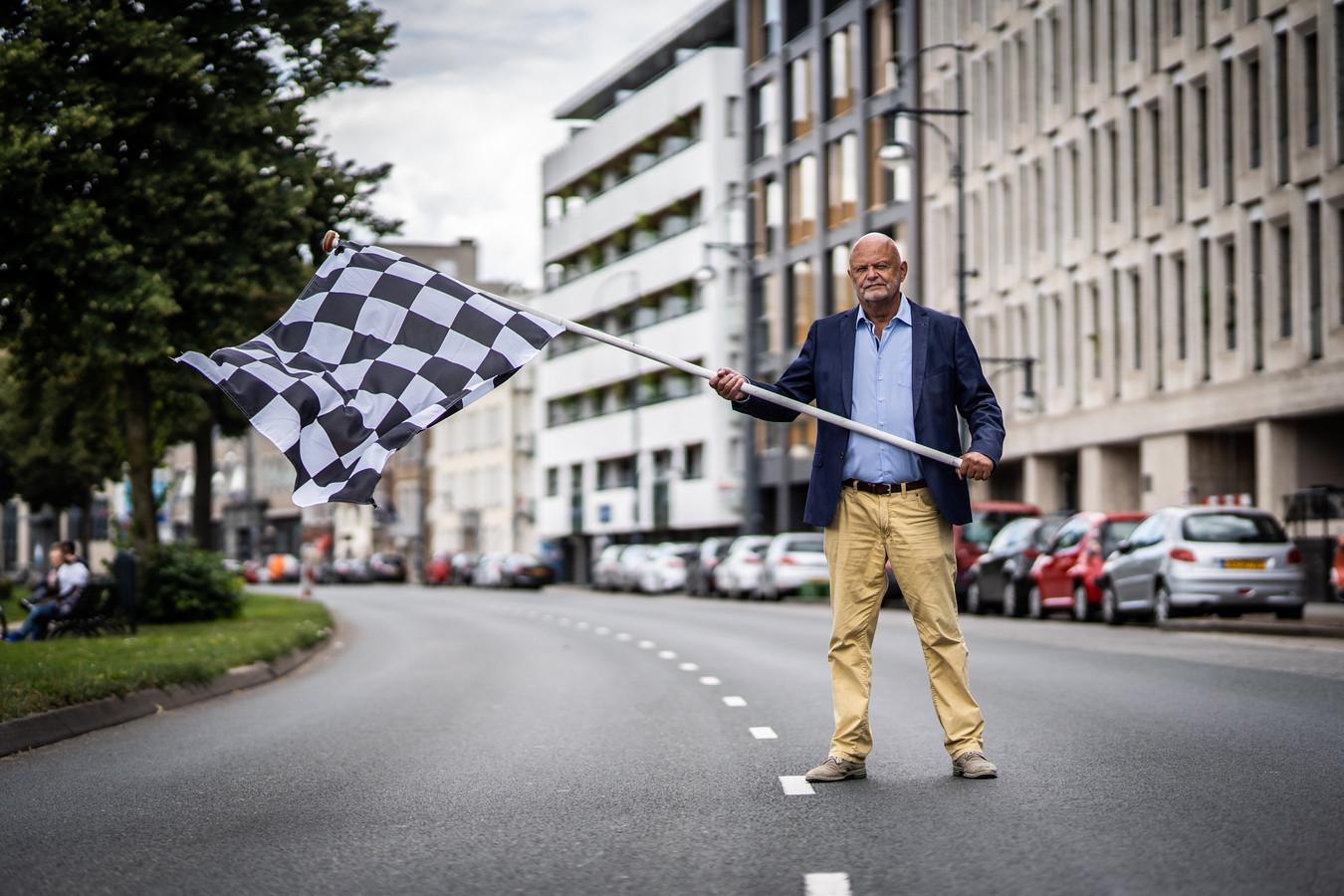 John Holtackers met de zwart-wit geblokte finishvlag die hij uit protest tegen snelheidsduivels op Arnhemse Centrumring aan zijn balkon heeft gehangen.