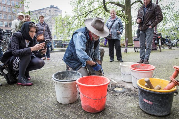 Gunther Demnig plaatst een struikelsteentje in de stoep bij Spinozastraat 7 in Amsterdam afgelopen april. In de hoofdstad liggen inmiddels vierhonderd struikelstenen.