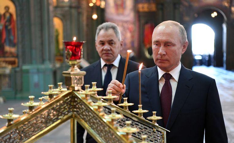 President Putin en de Russische minister van Defensie Sergei Shoigu brengen een bezoek aan de kathedraal van de opstanding van Christus, een Orthodoxe kathedraal in Moskou.  Beeld EPA