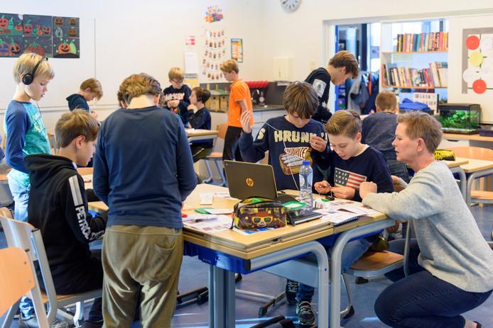 Juf Liesbeth Mol (rechts) is enthousiast over het 'atelierleren' op basisschool De Meent in Aalst.