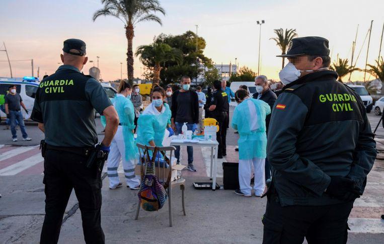Hulpverleners testen reizigers voor ze de boot naar Ibiza nemen.  Beeld EPA
