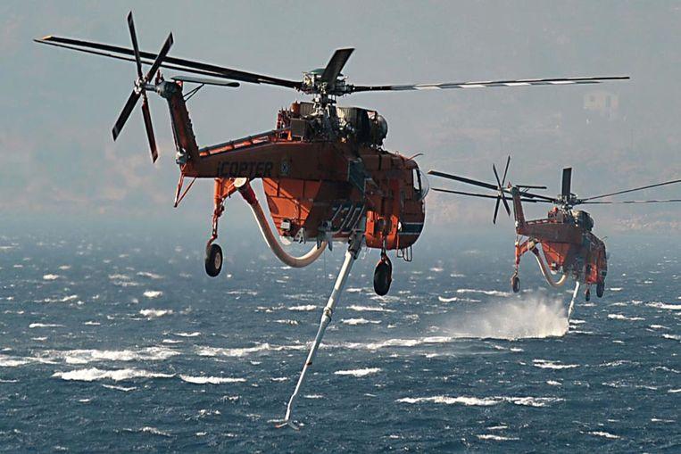 Blusheli's pikken water op ter bestrijding van de bosbranden in Athene. (AFP) Beeld AFP