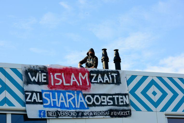 Op het dak van de nieuwe middelbare islamitische school protesteren twee mannen.  Beeld ANP