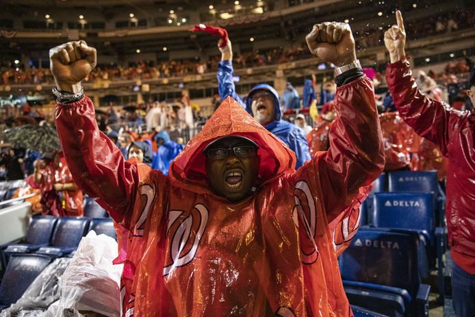 In de stromende regen vieren de fans van de Washington Nationals feest in hun eigen stadion, waar ze de beslissende wedstrijd van de World Series op een groot scherm hebben bekeken.