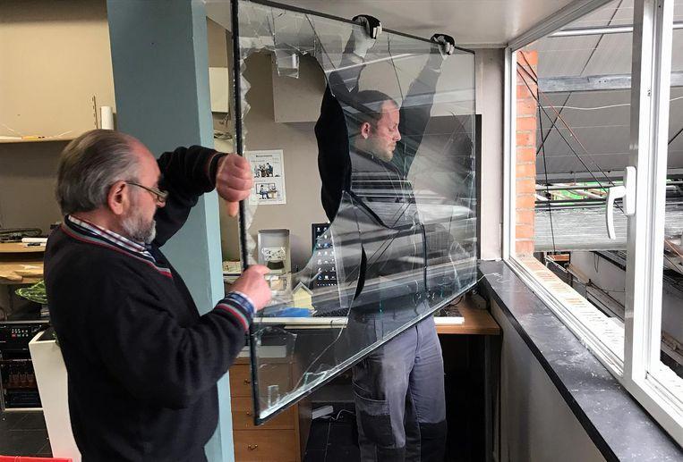 Zaakvoerder Eugeen Sels haalt samen met een glazenmaker een verbrijzelde ruit uit een raam van het kantoorgedeelte. De inbrekers hebben de ruit stukgeslagen.