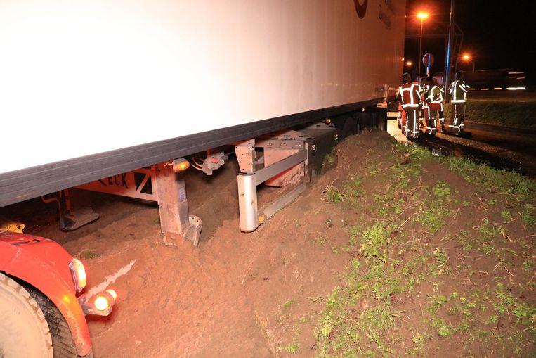 De vrachtwagen kwam vast te zitten op de aarden wal en moest met man en macht vrijgemaakt worden.