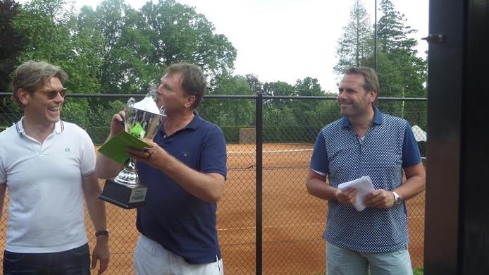 Eric Zwijnenberg kust de beker. Links Ready-voorzitter Koen Groenewold, rechts sponsor Erwin Brookhuis.