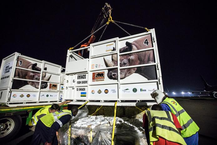 De containers worden op vrachtwagens geladen.