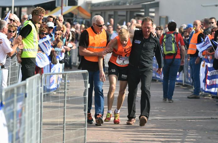 Beeld uit de Kustmarathon van 2015. Erwin Harmes krijgt in de laatste 100 meter hulp van Lein Lievense (rechts) en André Stroo.