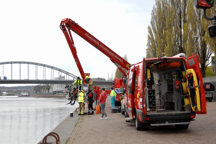 Brandweerduikers zoeken naar mogelijke inzittenden van de auto die vrijdagmiddag te water raakte op de Nieuwe Kade in Arnhem.