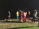 Een grote groep omstanders en hulpverleners staat op de wal.