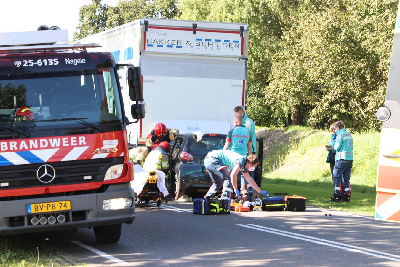 De automobilist moet door de brandweer uit zijn auto worden bevrijd. Ambulancepersoneel staat klaar om hem naar het ziekenhuis te brengen.