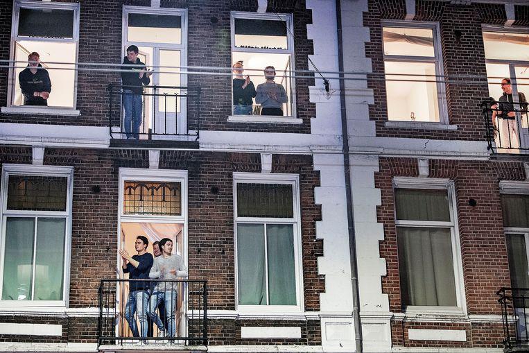 Bewoners van de Van Woustraat in Amsterdam klappen voor zorgpersoneel. Beeld Guus Dubbelman / de Volkskrant