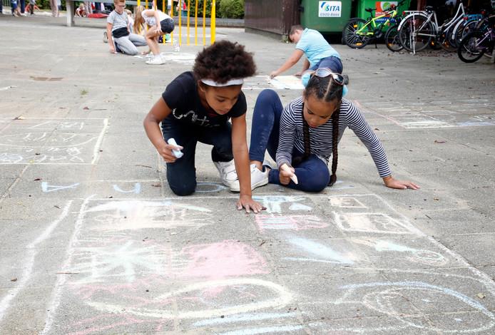 Ziona  (links) en Aliya tekenen de kermis van Nieuw-Namen op het schoolplein.