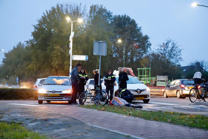 In afwachting van een ambulance is de fietser toegedekt met een deken.
