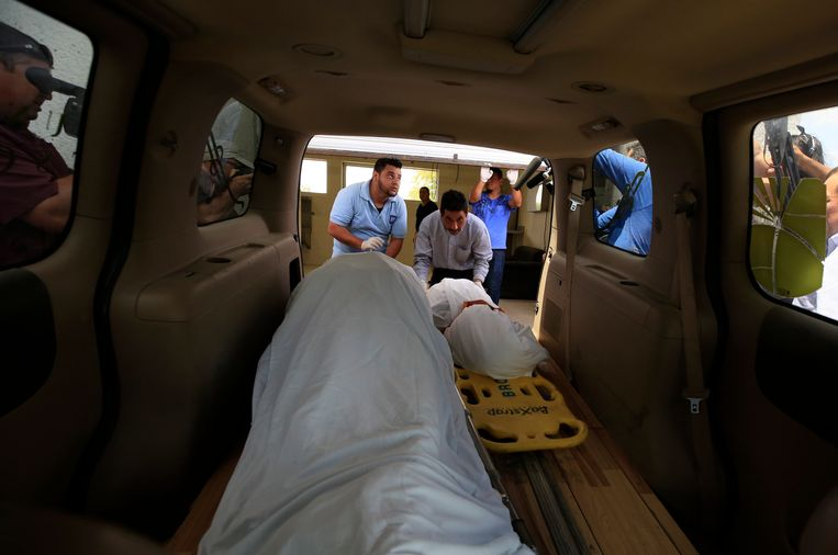 De lichamen worden in een busje van een uitvaartcentrum gelegd.