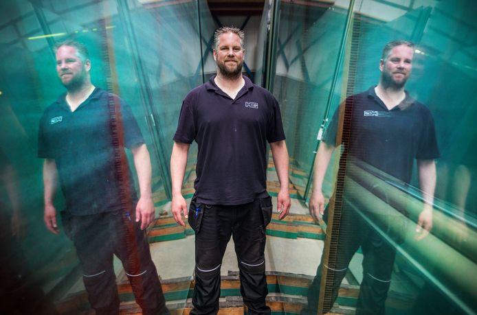 Peter Vrolijk tussen enorme glasplaten die staan in de hal van de Haagsche Glashandel.