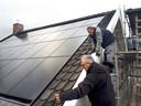 Verbouwing Koetshuis bij de Molenstraat, Karel Bartelen (onder) controleert met timmerman de dakpannen naast de zonnepanelen op het dak. Foto Alfred de bruin