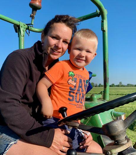 Emmy en haar zoontje Milan helpen de boer bij het aanleggen van een wintervoorraad hooi