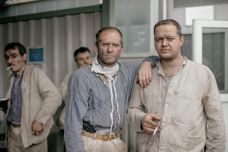 De mannen van de laatste kolenmijn kloppen 't zwarte stof van elkaars rug