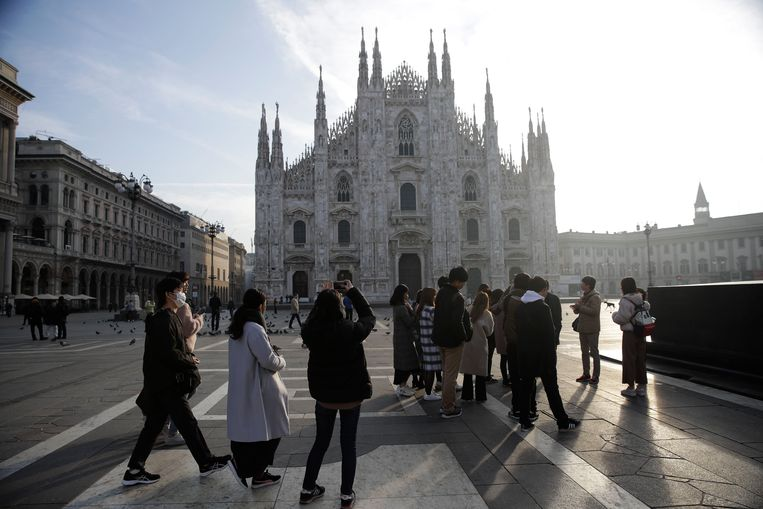 Toeristen fotograferen vanochtend de Duomo kathedraal in Milaan. In het noorden van het land groeit de ongerustheid vanwege nieuwe besmettingen met het coronavirus. Beeld AP
