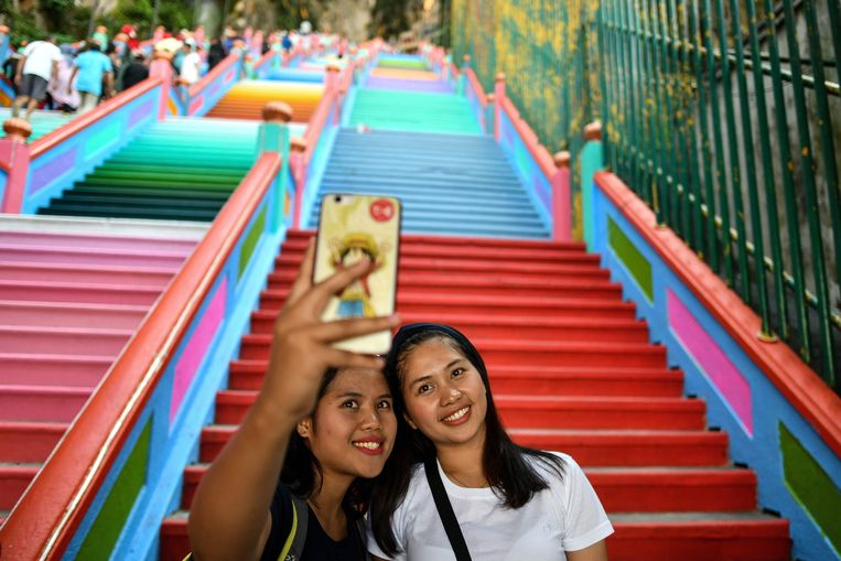 Two women take selfies in front of the newly-painted 272-steps staircase leading to Malaysia's Batu Caves Hindu temple in Kuala Lumpur on August 30, 2018. (Photo by Manan VATSYAYANA / AFP)