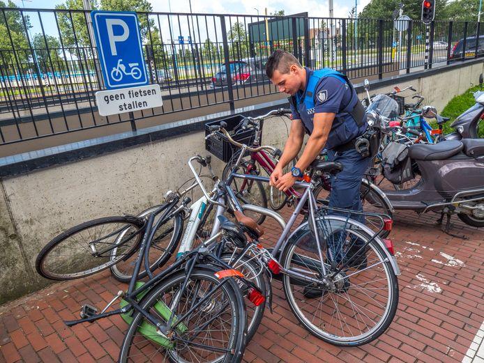 Een handhaver haalt verkeerd gestalde fietsen weg in het Stadshart.