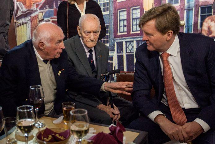Dachau-overlevenden Jan van Kuik (links) en Jan de Vaal (midden) in het Verzetsmuseum in gesprek met koning Willem-Alexander.