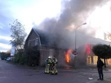 Uitgebrand winkelpand in Putten wordt gesloopt; voorgevel met shovel naar beneden gehaald