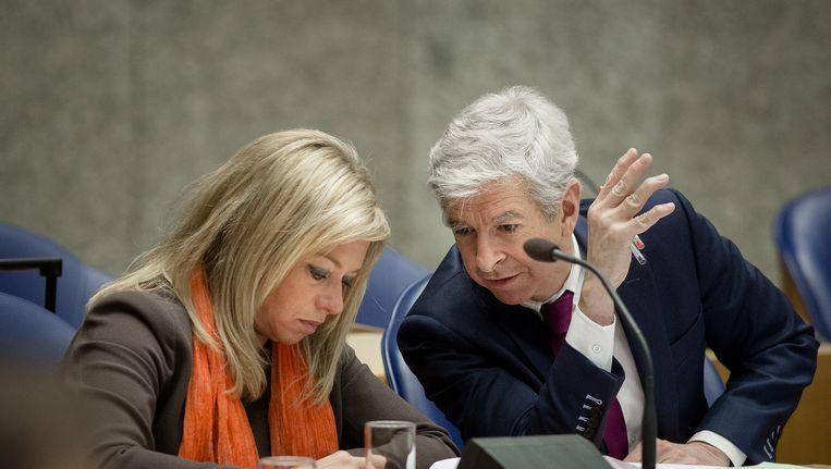 Minister Jeanine Hennis-Plasschaert (L) van Defensie in gesprek met minister Ronald Plasterk van Binnenlandse Zaken tijdens een debat over afluisterpraktijken in 2014 Beeld anp