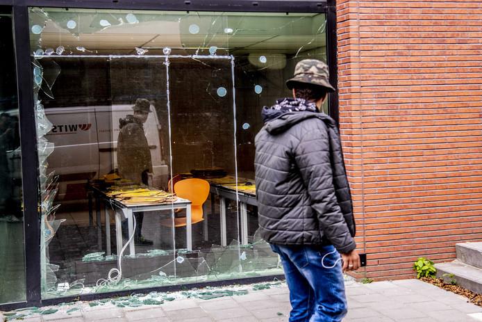 Een voorbijganger bekijkt de plek waar een kantoorpand is beschoten met een antitankwapen.