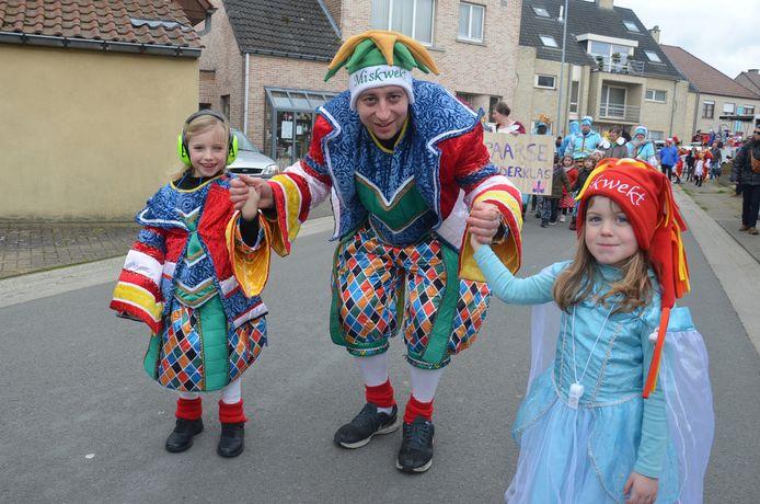 De kinderstoet in Iddergem: Een carnavalist van Miskwekt met twee kinderen van de gemeentelijke basisschool.