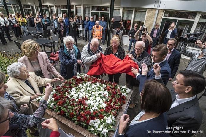 Een bed winterviolen ter nagedachtenis aan directeur Willem Marcelis. Tuinmannen Nico van 't Veer en Arnold van Kouwenhoven onthullen het samen mets stadsdeelwethouder Jurgen van Houdt.