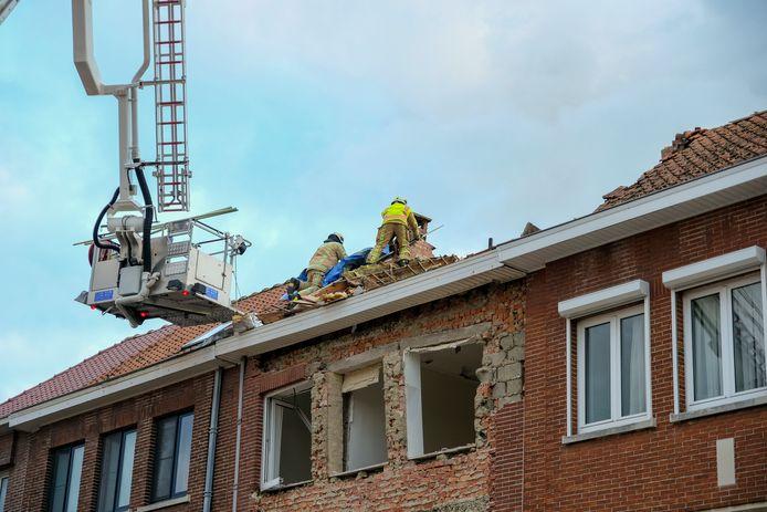 De brandweer legt een zeil op het beschadigde dak.