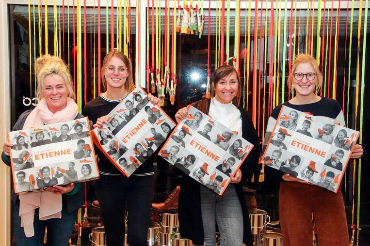 Sybille Renier (tweede van rechts) showt samen met teamleden Joke Dutry, Sanne Vanderhaeghe en Josefien Vandepitte de nieuwe zak van Schoenen Etienne. Daarop staan foto's van trouwe klanten. Bea Moortgat ontbreekt op de foto.