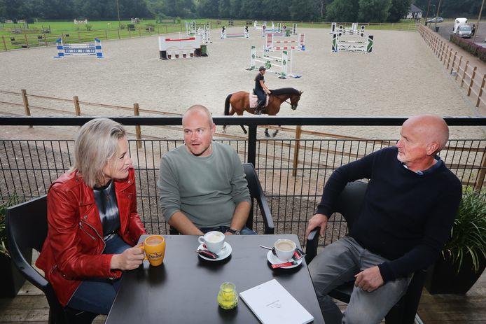 Wanda den Ridder, Sepp Voesenek en Jack Leemans (v.l.n.r.) op het dakterras bij ruitersportcentrum De Roosberg. Op de achtergrond de nieuwe buitenpiste met daarnaast het derbyterrein, een ode aan het voormalige Breda Outdoor.