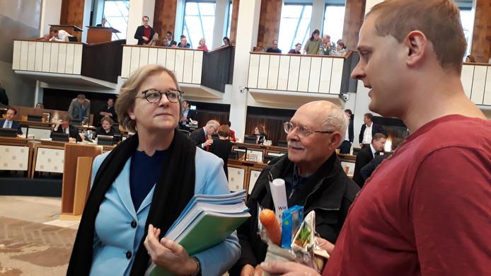 VVD-gedeputeerde Bieze (links) krijgt van leden van het buscomité Aldenhof een schoen met wortel en de wens voor uitbreiding van buslijn 4.
