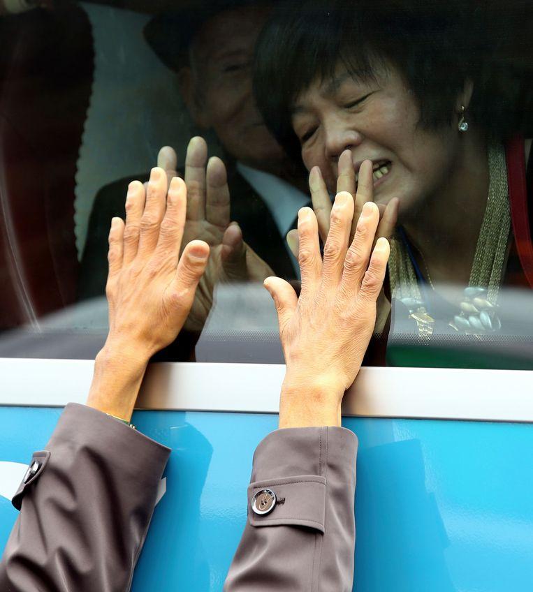 Een Zuid-Koreaanse vrouw en een Noord-Koreaans familielid nemen afscheid van elkaar na een familiehereniging in Noord-Korea. De meeste herenigingen duren maar kort en elkaar weerzien is gezien de formele staat van oorlog tussen beide landen onwaarschijnlijk. Beeld AP