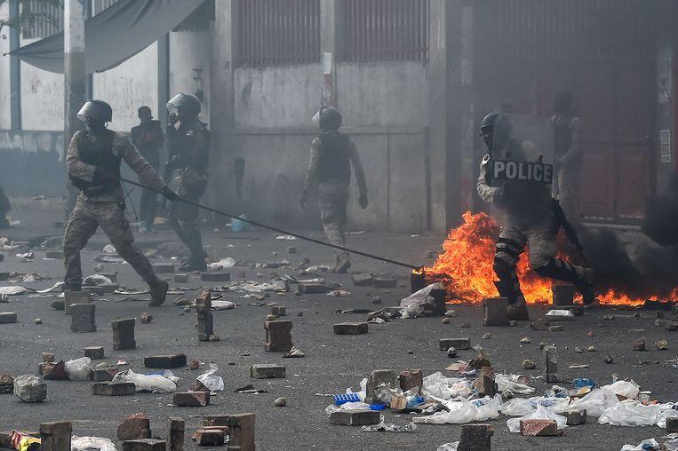 Politieagenten ruimen de straat op na de protesten.