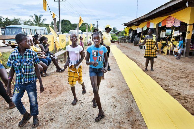 Marronkinderen lopen langs de gele loper die is uit gelegd voor Ronnie Brunswijk, lijsttrekker van de ABOP. Beeld Guus Dubbelman / de Volkskrant