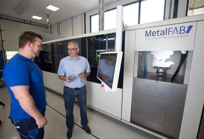 Lodewijk van der Borg met in zijn hand een onderdeel dat operator Bob van Lochem (l) in de machine van Additive Industries heeft gemaakt. Foto Theo Kock