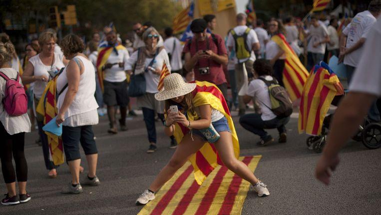 Een vrouw met de Catalaanse onafhankelijkheidsvlag om haar schouders in Barcelona tijdens de Catalaanse Nationale Feestdag. Beeld AFP