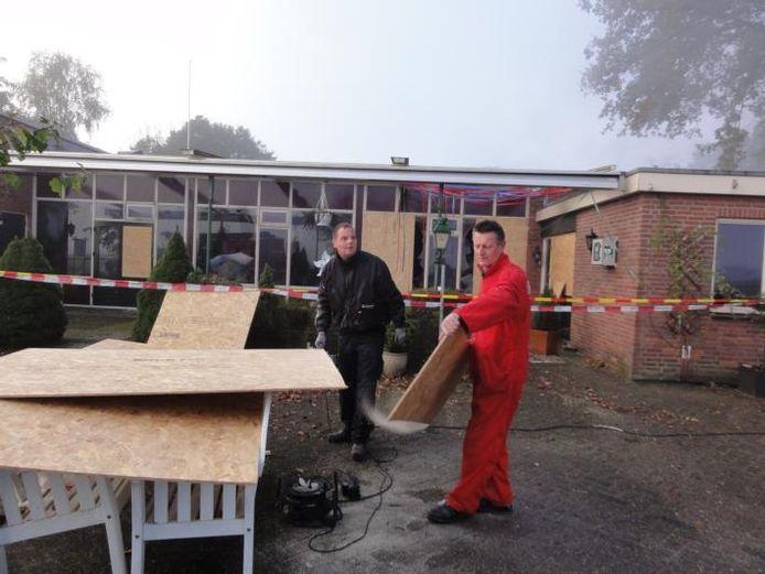 Medewerkers van het reinigingsbedrijf timmerden na de brand de gebroken ruiten van de Dalmshoeve af. foto Sandra Veltmaat